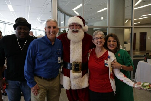 Santa Poses with Dr. Roche, Magaly Hernandez, and Others